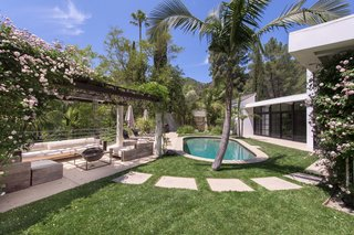 A small pool is located just a few steps away from the living room. A flower-covered trellis offers a canopy for alfresco dining and lounging.