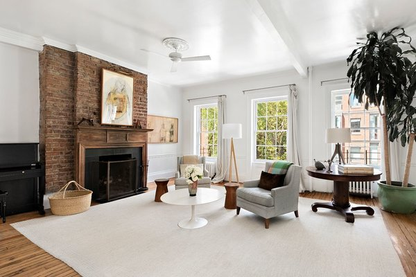 Soaring ceilings continue into the airy upper-floor living room, complete with large, north-facing windows and an anchoring exposed brick fireplace.