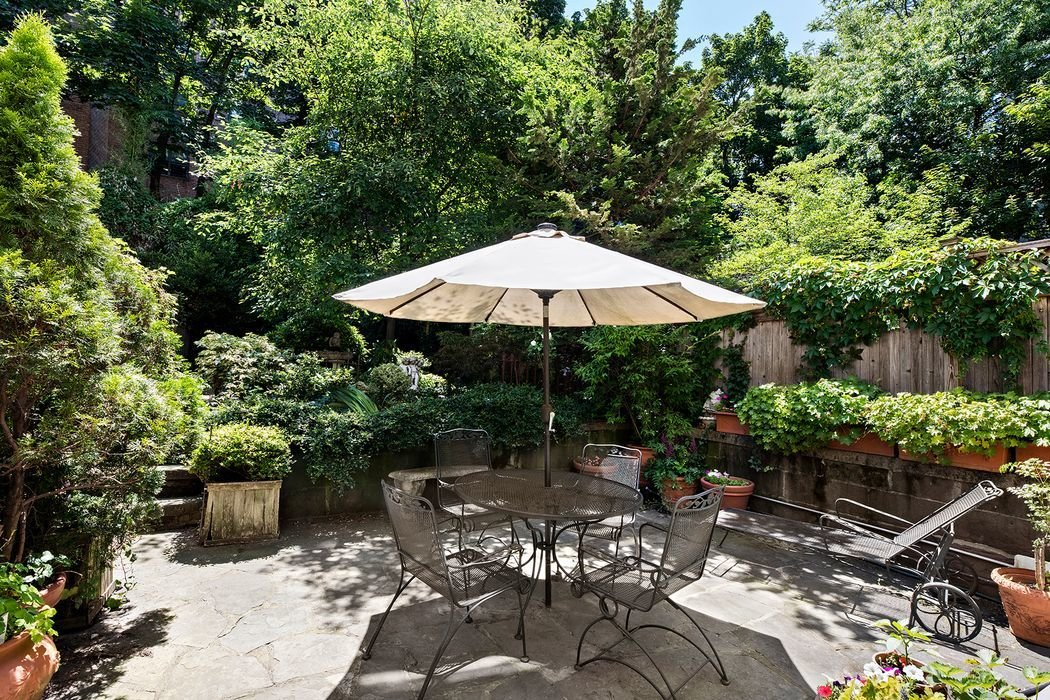 "Outdoor, Back Yard, Trees, Stone Patio, Porch, Deck, Vertical Fences, Wall, and Small Patio, Porch, Deck A lushly landscaped garden awaits in the backyard. Featuring a fountain and small pond, the outdoor area provides a serene oasis in the middle of Manhattan.  Photo 7 of 7 in Elaine's Townhouse From ""Seinfeld"" Wants $8.65M"