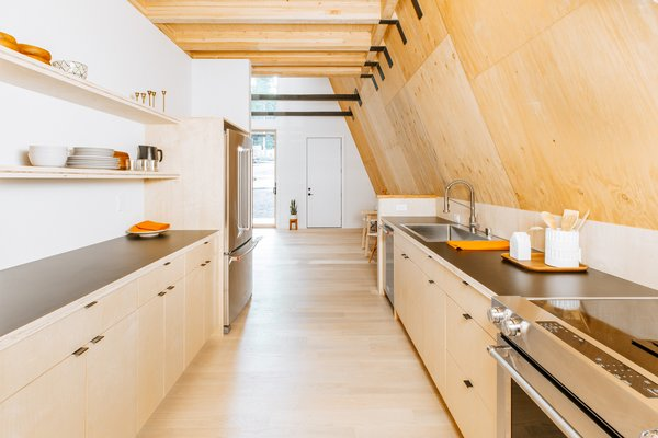 The large galley kitchen lies steps away from the living room. Pale Birch cabinets on both sides of the room provide plenty of storage and counter space.