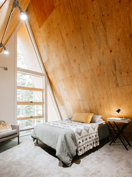The second bedroom is located beneath the A-frame's apex. With floor-to-ceiling windows, the nook is a cozy yet bright place to start and end each day.