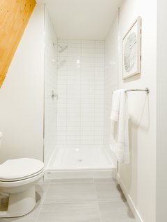 Subway tiles line the standing shower in the crisp, white bathroom.