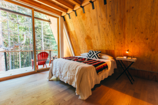 Exposed wood finishes continue into the bedrooms. Large, sliding doors frame picturesque views of the forest waiting outside.