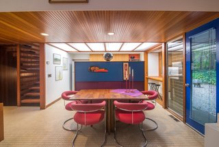 The home features beautifully restored wood paneling, and it's filled with unique midcentury furniture. Here, a retro dining set complements the geometric elements found throughout the interior.