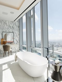 The home offers a total of six and a half bathrooms, this one with a free-standing soaking tub from which one can enjoy expansive views out over San Francisco. Marble-clad flooring and walls complete the industrial-chic vibe.
