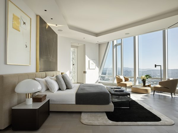Here, a look at one of the four bedrooms, all of which offer views of the city from bed. The building's iconic diagonal beams swipe across the facade of looking glass.
