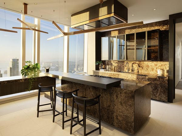 A monolithic stone kitchen with Emperador marble also features a wood bar top that stretches to connect a narrow counter along the window. Rossana cabinets with backlit bronze mirrored glass complement the decorative light fixtures by Henge.