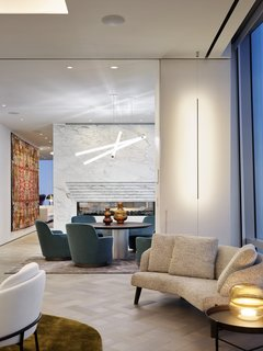 An informal dining area sits opposite the see-through fireplace. The more intimate space features a Swarovski Voltaire pendant light, along with chairs by Minotti Jacques and a custom table by Henge.