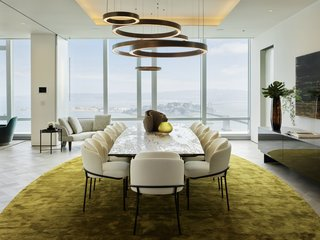 The formal dining room offers an acid-washed S-Penny Henge dining table that seats 12, surrounded by Minotti Fil Noir black and gold frame dining chairs. The burnished-brass ringed lighting is also by Henge.
