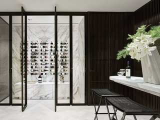 Along the back wall of the dining area is a glass-walled Rimadesio wine cellar. The suspended Calcatta marble tasting area is complete with Bottega Veneta black leather barstools.