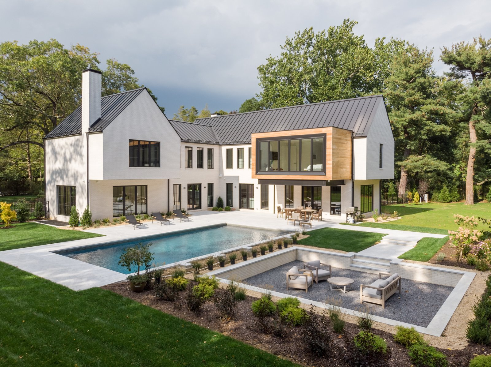 Exterior, Metal Roof Material, Gable RoofLine, and House Building Type A look at the rear of the home, which connects several geometric forms around the open corner concept. The interior seamlessly flows outward to meet a large patio, pool, and sunken entertainment area.  Photo 11 of 11 in This Home's Unique Shape Is Designed to Capture Sunlight