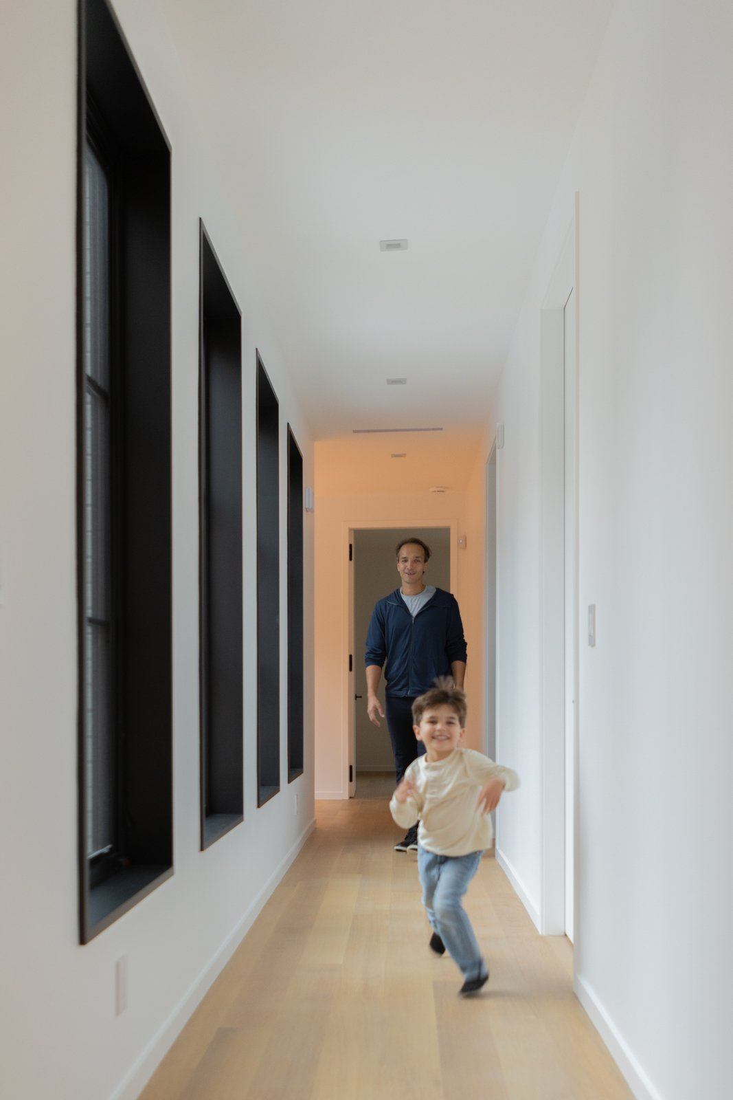 Hallway and Light Hardwood Floor Simply trimmed white walls and light, natural hardwood floors create a cohesive feel throughout the home.  Photo 9 of 11 in This Home's Unique Shape Is Designed to Capture Sunlight