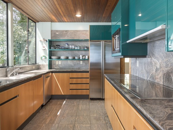 In the newly remodeled kitchen, teal shelves add a playful touch of color, contrasting with the neutral palette of the lower wood cabinets, granite countertops, and stainless-steel appliances.