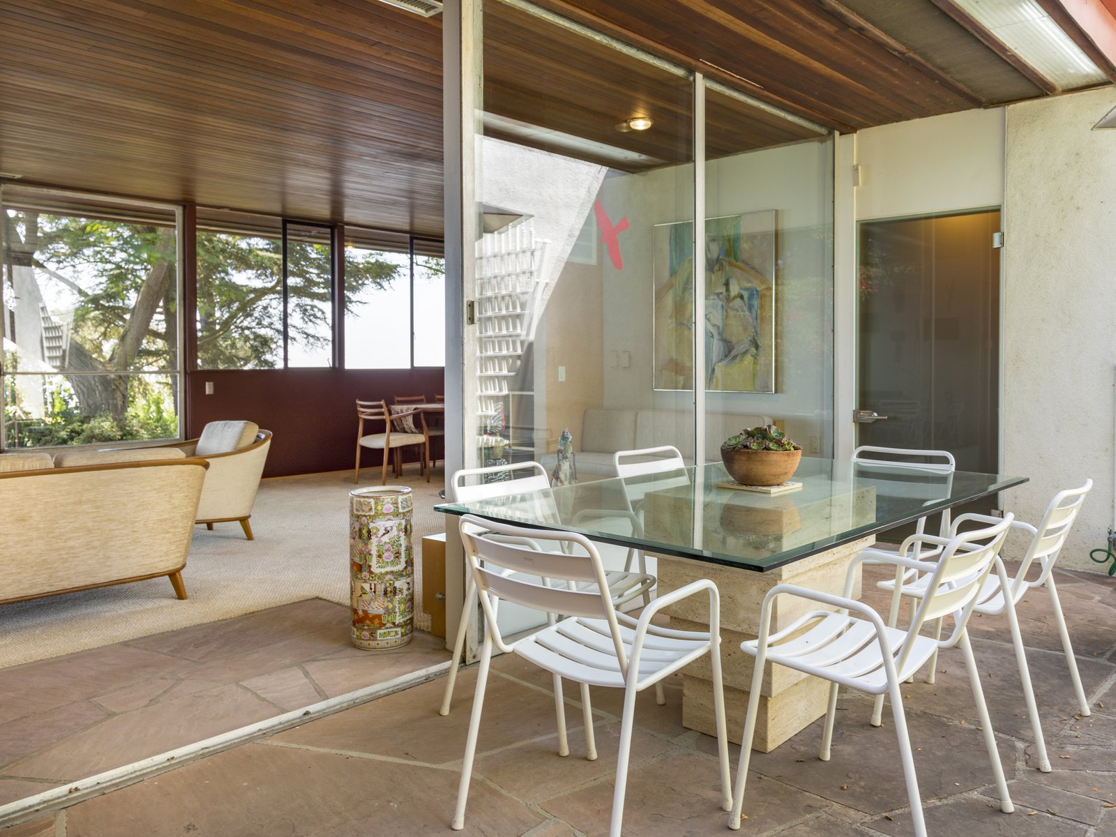 Outdoor, Side Yard, Small, and Stone Large glass windows and doors optimize cool ocean breezes and usher in an abundance of natural light, highlighting the home's clean lines and minimalist design.  Best Outdoor Stone Small Photos from Own This Neutra-Designed Midcentury Stunner for $2M