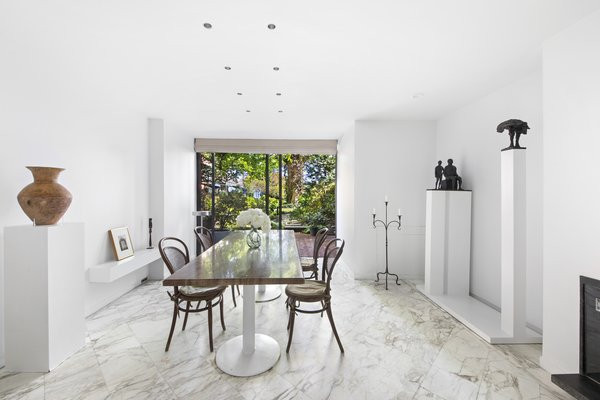 Marble lines the floor of the home's formal dining area, while oversized glass doors frame views out to the garden. The space is large enough to accommodate easy entertaining.