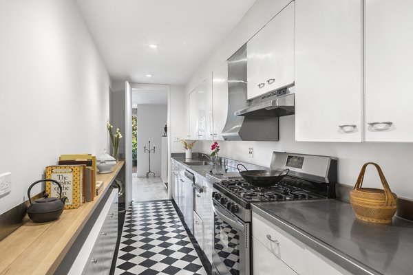 A galley kitchen—equipped with stainless-steel appliances and countertops—is located on the garden floor and accessed from the main foyer. Steps away is a large pantry that includes additional cabinetry, as well as another sink.