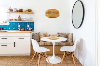 A built-in wooden bench right off the counter completes the cozy dining nook in the corner.