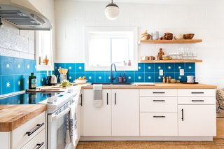 Featuring an eye-catching backsplash, the bright, airy kitchen also includes custom cabinetry.