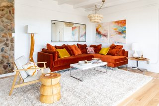 Keeping in line with its dramatic facade, the home boasts a crisp, vibrant palette throughout. A moody-red velvet sectional provides ample seating in the main living room, while a shaggy, cream-colored rug adds an additional level of texture.