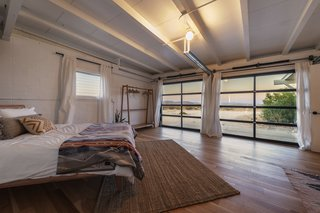 In the master bedroom, a wall of glass windows effortlessly frames gorgeous desert views. The second of the three bedrooms includes an en-suite bath, as well as a laundry area.