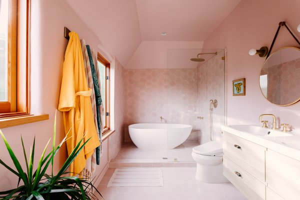 Along with a walk-in closet, the master suite includes a tranquil, spa-like bathroom. Blush pink walls encapsulate a large, freestanding tub.