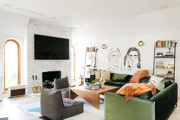 In the living room, tall leaning shelves frame handcrafted artwork. A geometric bronze coffee tables complements the green velvet sectional, which offers plenty of space to gather.