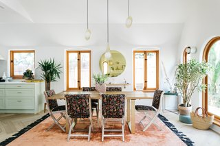 Steps from the kitchen is a large dining area, complete with floral-upholstered chairs.