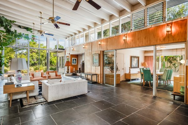 A band of clerestory windows runs along the south side of the garden room. Sliding glass doors separate the space from a formal dining area.