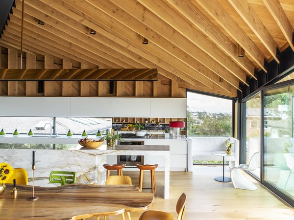 The kitchen sits beneath rafters of Douglas fir on the top floor. The counter and cabinets are by Varenna for Poliform, the bar stools are by Bassam Fellows, and the side chair is by Verner Panton for Vitra.