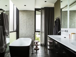 The master bathroom features a freestanding tub by Teuco and cabinetry designed by Clive.