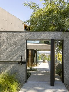 """Many of Los Angeles's iconic modern houses float above the city like tethered spaceships on stilts,"" says Clive. ""I had always yearned for the opportunity to design my own floating home."" Custom black zinc panels and sandblasted concrete form the exterior."