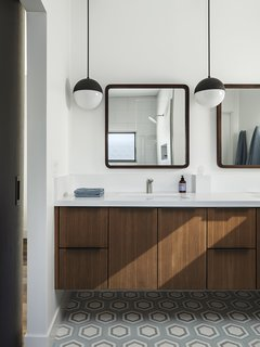 The master bathroom features custom walnut cabinetry and Cedar & Moss Globe pendants from Rejuvenation.