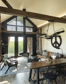 A hanging fireplace from Fireorb anchors the living area, where Book Totem and Peace Sign, both by Karen, are on display. A Graffiti pendant by Hubbardton Forge hangs over a custom table by Jed Dawson.