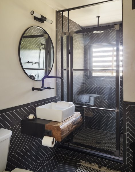 The bathroom includes a faucet and sink from Kohler, shower fixtures from Brizo, and a mirror and light from Restoration Hardware. The tiles are by Ann Sacks.