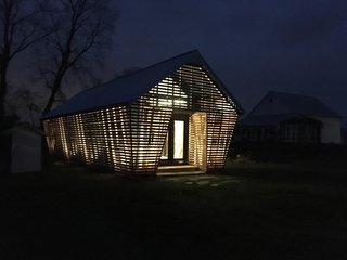 "Lit from within, the guesthouse is a welcoming beacon in the night. ""It's nice to show that this kind of agricultural vernacular can be a contemporary thing,"" says designer Jason Kentner."