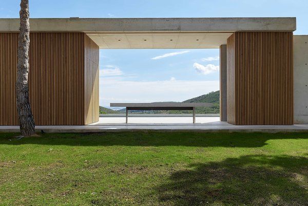 Breaking up the concrete form is a pergola-like resting area. Wood-clad walls on either side read as columns supporting an architrave.