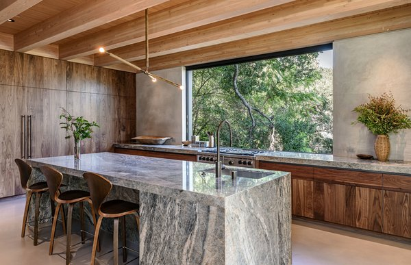The kitchen cabinets are black walnut with an oil finish, which Gnatovich and Rennalls chose to enhances the natural color of the wood. The countertop and island are Cielo Quartzite, while the backsplash is steel-troweled smooth stucco.