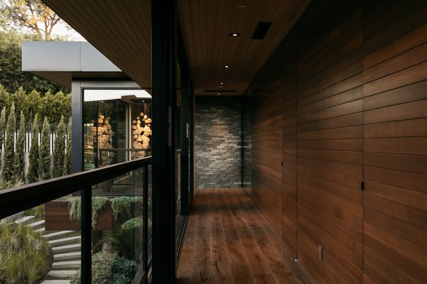 Glass sliders transform the second floor hallway into an open-air breezeway. The space overlooks the lush lawn and canyon views, adding to the treehouse-like feel.