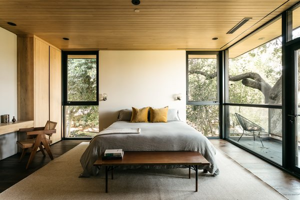 Several guest bedrooms are tucked under an impressive 100-year-old oak tree in the north corner of the lot. This one features a private balcony and floor-to-ceiling windows flanking both sides of the bed.