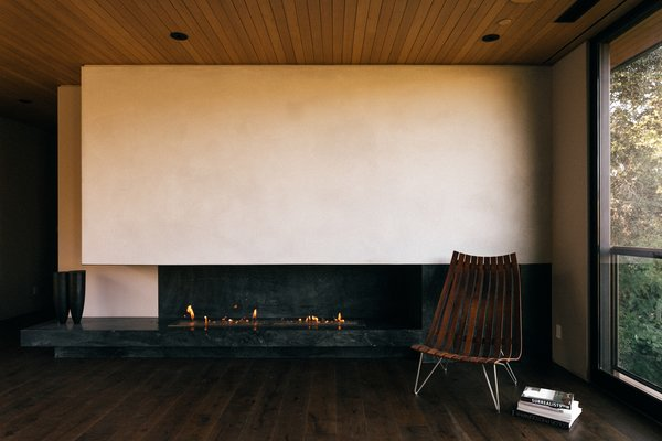 A floating soapstone fireplace wraps around a wall in the master bedroom.