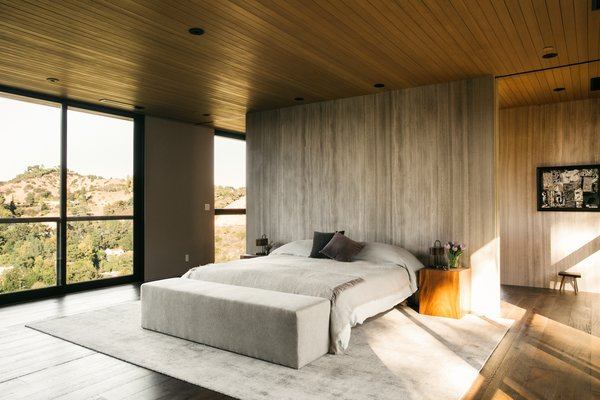 The nearly 1,000-square-foot master suite offers dual views from floor-to-ceiling windows. The bed is nestled against a warm, whitewood marble slab wall, which divides the bathroom area.
