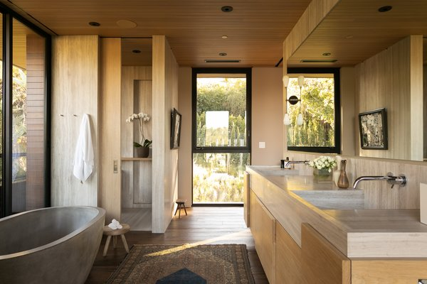 Whitewood marble continues into the spa-like master bathroom. The airy space features a white oak vanity, a marble slab shower, and a Native Stone concrete soaking tub overlooking the private balcony. The suite also includes a spacious closet with a glass-topped island.
