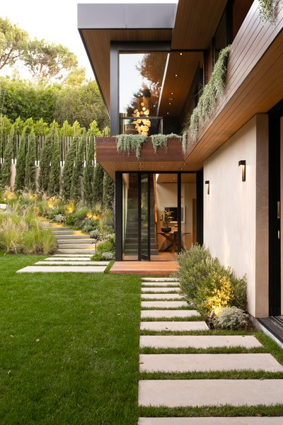 Paved stairs lead down to a lush lawn and the home's main entrance: a pivoting front door that opens to a two-story atrium. Greenery dangles from planters integrated into the second floor, while additional pavers connect two sliding glass doors in the living room.