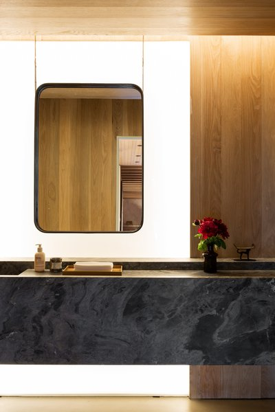 A look at a guest bathroom. The floating stone vanity is juxtaposed against wood panels and a backlit feature wall.