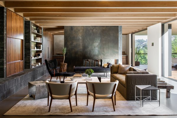 A handsome living room opens to the lawn via disappearing sliding glass doors, while a two-sided fireplace separates the space from the kitchen. The large seating area is bordered by built-in bookshelves and exposed wooden beams.