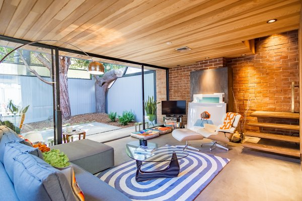 A look at the living room in the larger apartment. Full-width glass and sliding doors create an instant indoor/outdoor connection and provide direct access to one of the four private courtyards—a distinct feature of Ellwood's original design.