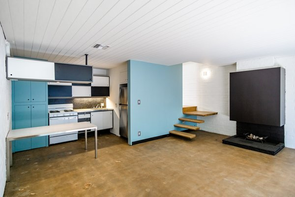 Inside the first of two smaller units, bright blue cabinets contrast with the white-painted brick and wood ceilings. The original fireplace serves as the main focal point in each of the apartments.