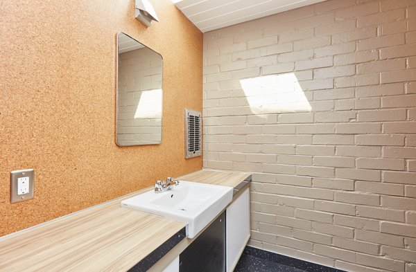 A look at one of the bathrooms. Exposed brick and the use of simple materials continues into this space.