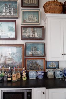 Along a corner wall in the kitchen, an array of antique ship paintings are stacked upward toward the ceiling.