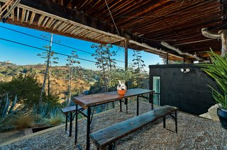 A covered terrace and studio nestled beneath the structure is also included in the sale.